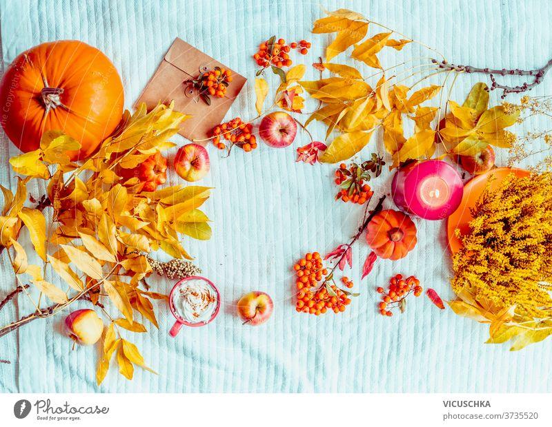 Herbstliche Stimmung. Verschiedene Herbstdekorationen. Kürbis, Tasse heiße Schokolade, Kerze auf blauer Strickdecke. Rahmen. Flach gelegt. Ansicht von oben