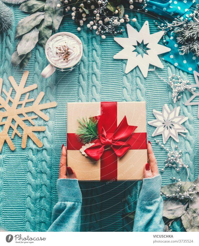Frauen reichen einen Pullover mit einem Weihnachtsgeschenk mit roter Schleife ein. Blaue Strickdecke mit Tasse Cappuccino. Schneeflocken und Winterdekoration. Ansicht von oben. Flach gelegt