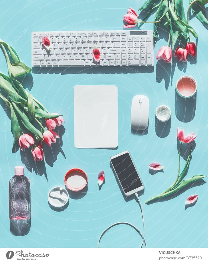 Frühjahrskonzept . Smartphone-Attrappe. PC-Tastatur, Tulpen und Naturkosmetikprodukte. Hellblauer Hintergrund. Lifestyle-Schönheitsblogging-Konzept. Flachlegen. Ansicht von oben