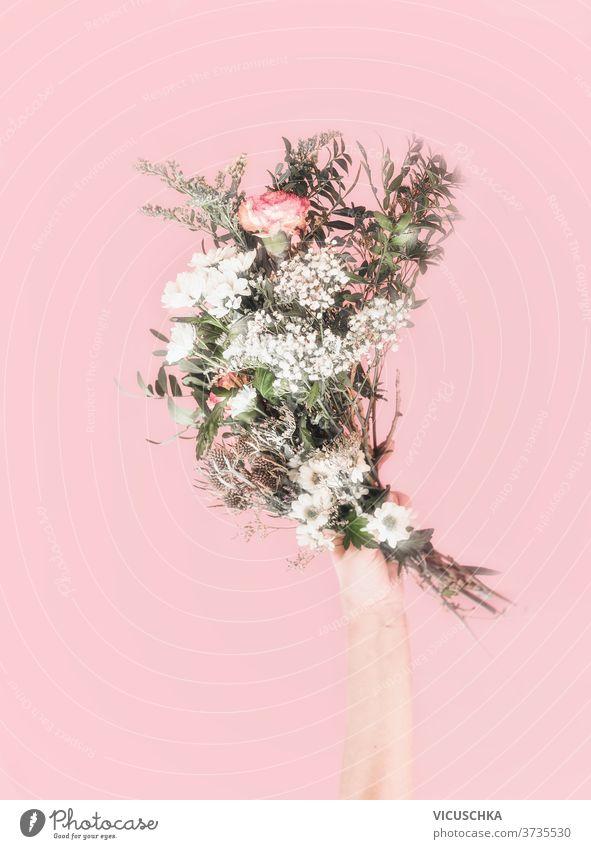 Frauen halten einen Strauss frischer Blumen in der Hand. Hellrosa Hintergrund. Romantisches Konzept. Vorderansicht . Pastell-Farbe Pastellfarbe Beteiligung