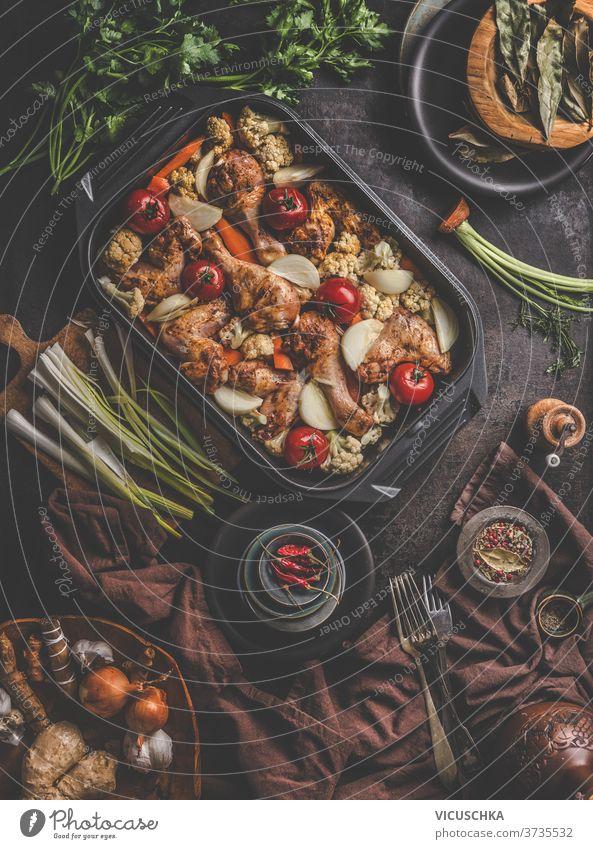 Frisch gekochtes Essen in einer Auflaufform mit verschiedenen Zutaten. Ausstattung der Küche. Dunkler Betonhintergrund, flach verlegt. Ansicht von oben