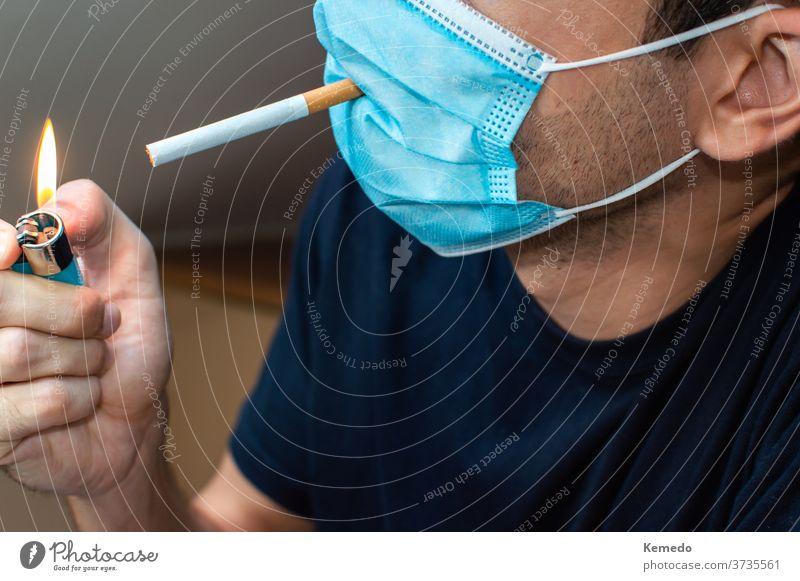 Junger Mann mit Maske zündet sich eine Zigarette an. Coronavirus lustiges Konzept COVID verrückt seltsam selten neue Normale Idiot dumm Person Mundschutz