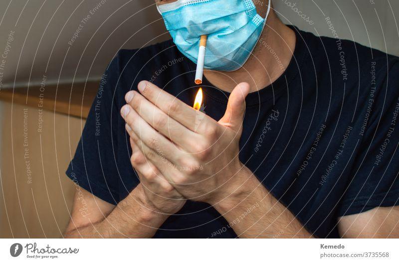 Mann zündet eine Zigarette an, während er eine Gesichtsmaske trägt. Covid komisches Konzept lustig Coronavirus Korona Bund 19 Mundschutz Person Rauch Freizeit