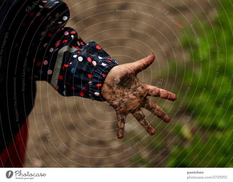 Eine matschige, dreckige Kinderhand. Kind spiel bei Regen in Regenbekleidung im Matsch kinderhand kindheit kinderspiel spaß regen regenkleidung regenjacke