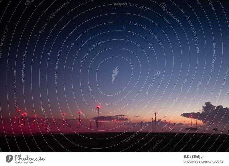 Mystische rote Punkte im Morgengrauen. Unter einem klaren Sternenhimmel schmiegt sich der aufsteigende Nebel an die beleuchtete Säulen des Windparks in Ostfriesland.