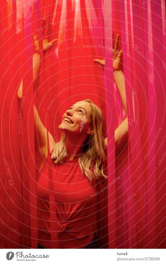 fröhliche junge Frau zwischen roten Streifen frau jubeln lachen junge frau entspannt glücklich Band Spaß single lächeln optimistisch Dekoration zuversicht