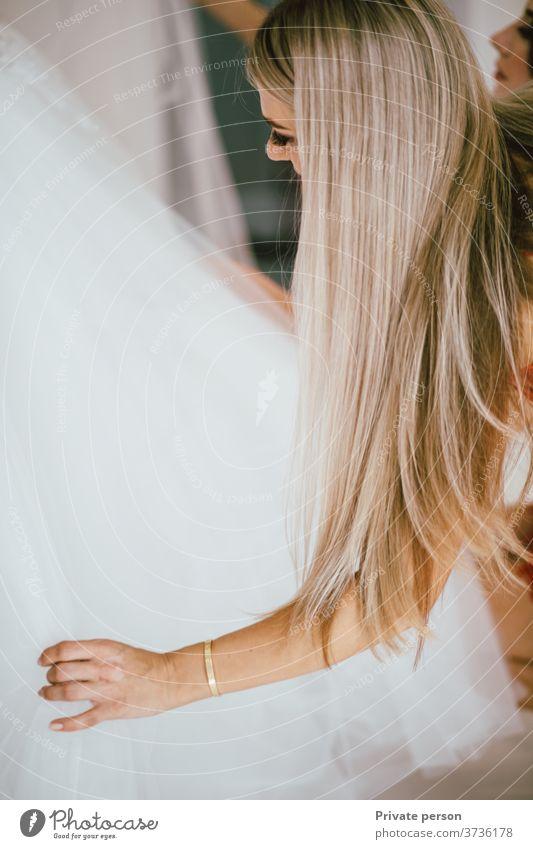 schöne junge Frau mit langen wallenden blonden Haaren untersucht weißes Brautkleid lange Haare Schönheit Mode-Modell Junge Frauen blondes Haar weißes Kleid