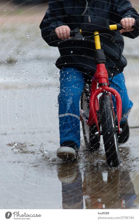 Kind auf Laufrad fährt mit Schwung durch die Pfütze Kinderspiel Kleinkind Pfützenbild spritzen Wassertropfen nass Spielen Kindheit Mensch Regen 1