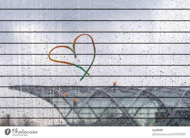Regenbogen Herz an verregneter Scheibe mit verschwommenem Blick auf moderne Architektur einer S Bahnhaltestelle regenbogenfarben herzförmig Verliebtheit