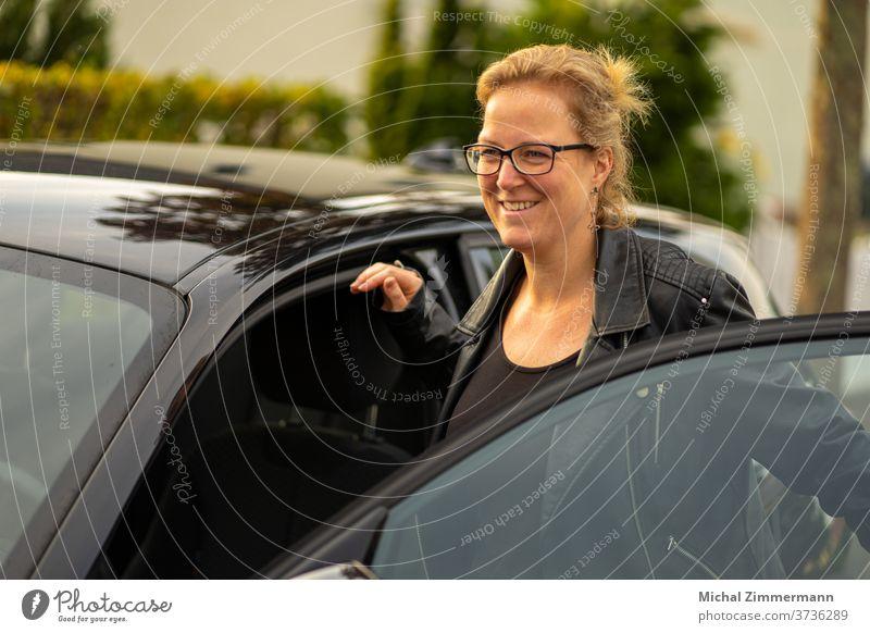 Junge Frau steigt in ein Auto Autofahren Verkehr Außenaufnahme Farbfoto Autotür PKW PKWs Verkehrsmittel Fahrzeug Dame Lederjacke Tag Frauengesicht Frauenbrust