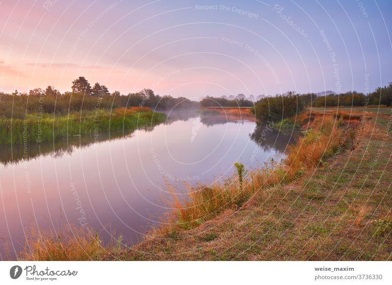 Nebliger Sonnenaufgang im Herbst am Fluss. Farbenfrohe Morgendämmerung. Bewölkter Sonnenaufgang. Reflexion & Spiegelung Himmel im Freien Natur Landschaft reisen