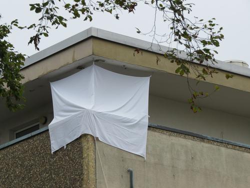 Improvisierter Sichtschutz an einem Eckbalkon Laken Schutz Improvisation Strukturen & Formen Tag Licht & Schatten Balkon Flachdach Hausecke Obergeschoß Beton