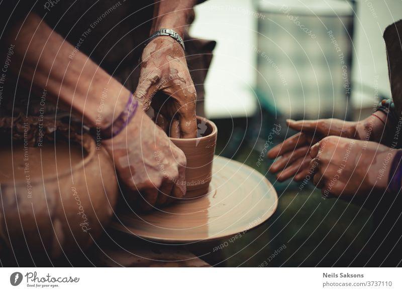 Nahaufnahme der Hände eines Töpfers und seines Schülers beim Töpfern lernen Töpferwaren Ton Rad Handwerk Topf Kunst Keramik Arbeit Basteln Fähigkeit