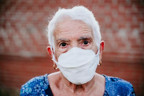 Porträt einer alten Dame mit Schutzmaske. neu normal alte Dame Corona-Virus Holunderbusch 80s Großmutter Frau älter heimwärts weiße Haare graue Haare mental