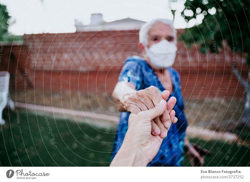 alte Frau mit Schutzmaske, die mit einer nicht erkennbaren Frau Händchen hält. Neues normales Konzept Dame Händchenhalten jung zwei Generationen mir folgen