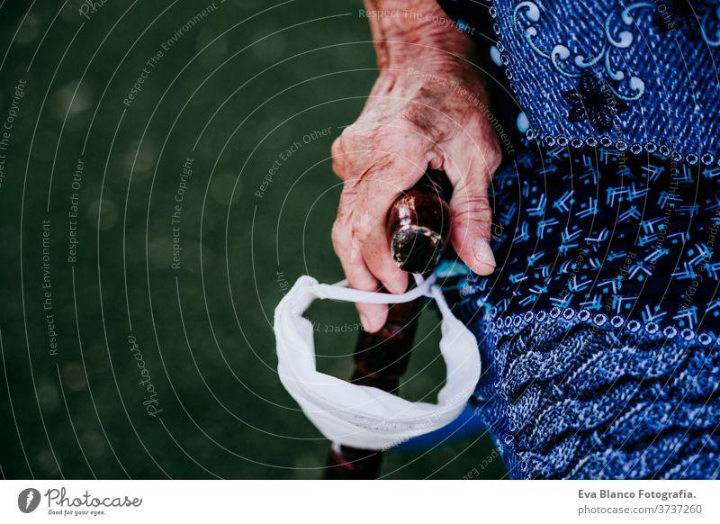 Nahaufnahme der Hände einer alten Dame, die einen Stock und eine Schutzmaske im Freien hält. neu normal alte Frau abschließen kleben neue Normale Hand Porträt