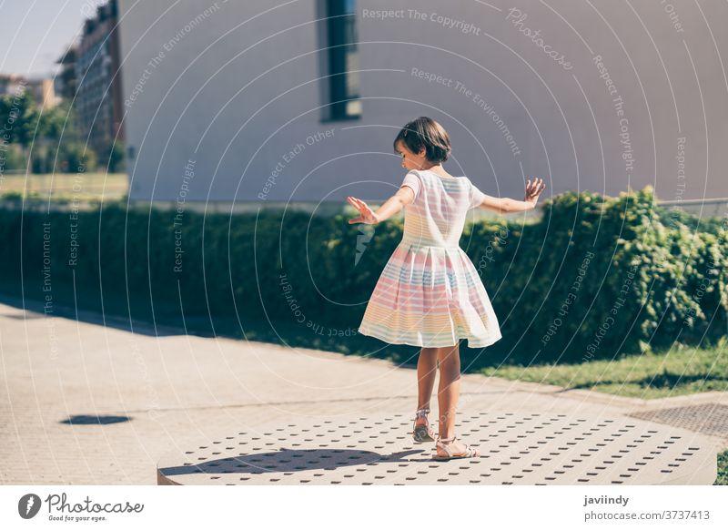 Glückliches 9-jähriges Mädchen in einem hübschen Kleid spielt Kind wenig urban Sommer niedlich Großstadt Frau jung Stil Kindheit Mode Straße schön Lifestyle