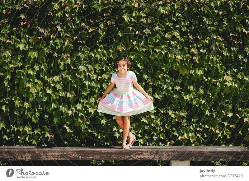 Glückliches 9-jähriges Mädchen in einem hübschen Kleid spielt Kind wenig Blätter Wand urban Sommer niedlich Großstadt Frau jung Stil Kindheit Mode Straße schön