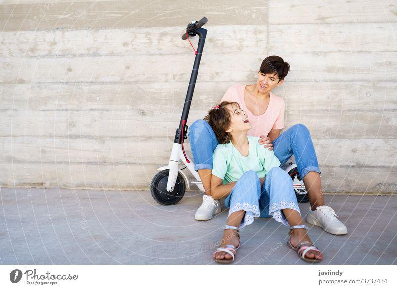 Mutter und Tochter sitzen auf einem Elektroroller Tretroller elektrisch Mädchen Frau Öko Transport urban Lifestyle modern Freizeit Großstadt Mitfahrgelegenheit
