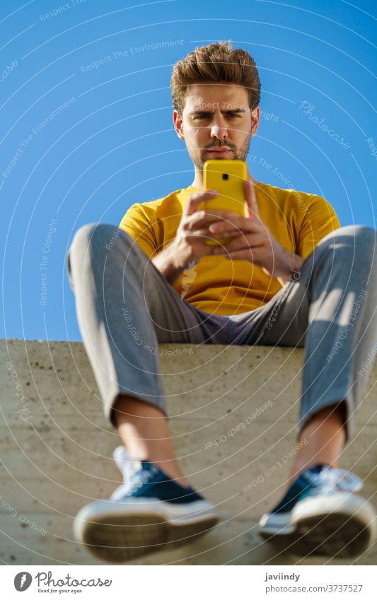 Mann benutzt sein Smartphone und sitzt draußen auf einer Kante männlich Lifestyle im Freien jung klug Telefon Typ Frisur Zelle Hintergrund modern lässig