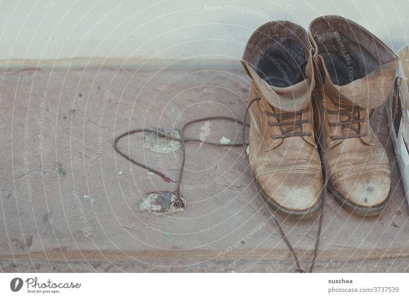 alte schuhe stehen auf einem fenstersims zum mitnehmen Schuhe Schnürschuhe gebraucht second hand Abnutzung zum verschenken Schnürsenkel Schnürstiefel Brauntöne