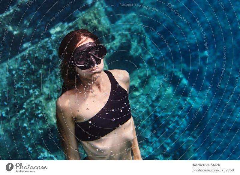 Junge Frau in Tauchermaske schwimmt unter Wasser Mundschutz Schutzbrille Schnorchel Tauchgerät schwimmen MEER Meer jung Sauberkeit durchsichtig Sinkflug