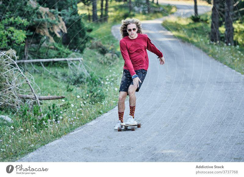 Junger Mann fährt Skateboard im Park Mitfahrgelegenheit Hipster Straße Sommer trendy ausgefallen Skater männlich Schlittschuh Stil Hobby modern aktiv Aktivität