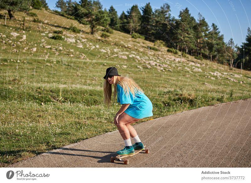 Frau fährt Skateboard entlang der Straße in den Bergen Skater Mitfahrgelegenheit Hipster Berge u. Gebirge Sommer jung Schlittschuh Wochenende ländlich Sport