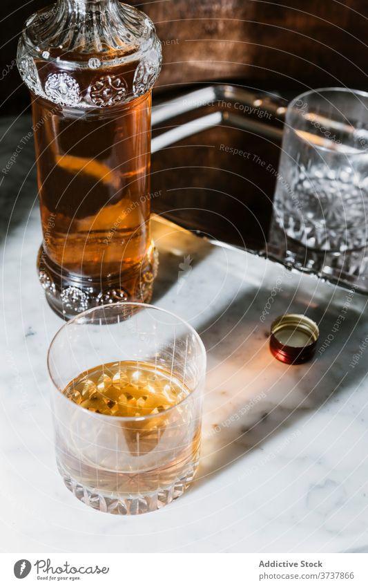 Glas mit alkoholischem Getränk auf Marmortisch Whiskey Bar Alkohol trinken Flasche dienen Abfertigungsschalter Schnaps Erfrischung Tisch Pub durchsichtig modern