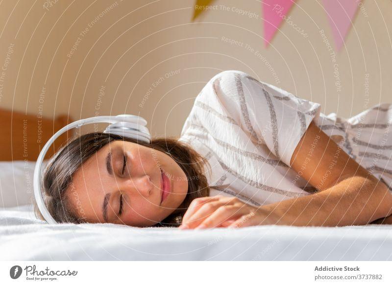 Junge Frau beim Musikhören auf dem Bett zuhören Kopfhörer heimwärts gemütlich Wochenende Augen geschlossen ruhen Lügen Apparatur Gerät Schlafzimmer jung
