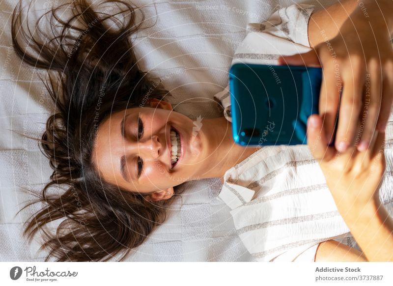 Fröhliche Frau mit Smartphone auf dem Bett sich[Akk] entspannen heimwärts unterhalten Lächeln Talkrunde benutzend soziale Netzwerke Lügen weich Internet Browsen