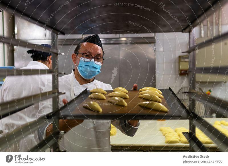 Ethnischer Mann beim Brötchenbacken in der Bäckerei Gebäck Koch vorbereiten medizinisch Mundschutz Coronavirus Teigwaren roh männlich ethnisch geschmackvoll