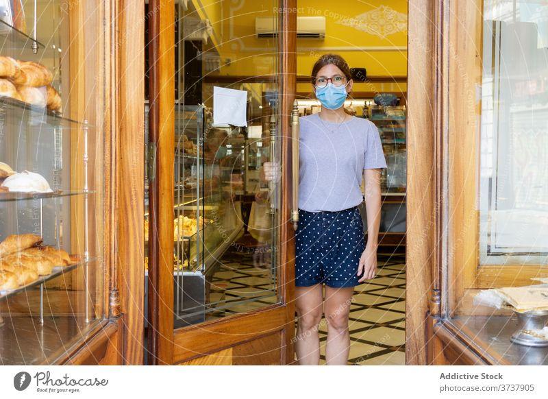 Frau mit Maske in der Bäckerei Verkäufer Innenbereich Tür Türöffnung Mundschutz medizinisch COVID gemütlich stehen neue Normale Sicherheit Personal behüten