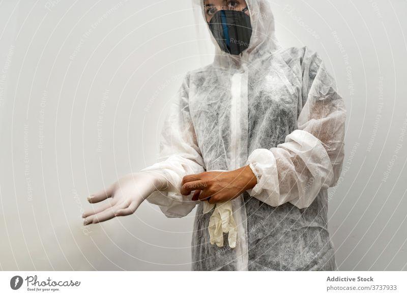 Arzt im PSA-Anzug zieht Handschuhe an Sanitäter Coronavirus behüten Mundschutz angezogen COVID ansteckend Sicherheit ppe Frau Medizin medizinisch professionell