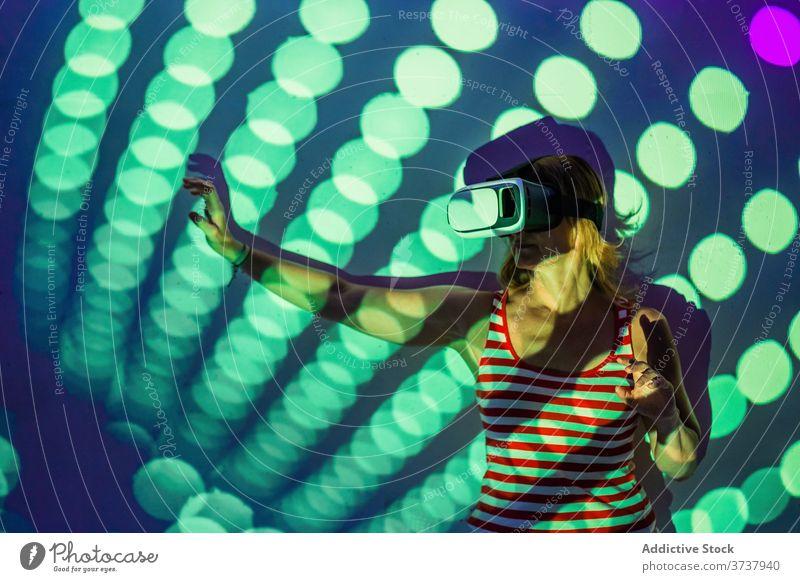 Frau in VR-Brille erkundet virtuelle Realität Virtuelle Realität Headset Schutzbrille berühren Erfahrung erkunden leuchten Projektor Technik & Technologie