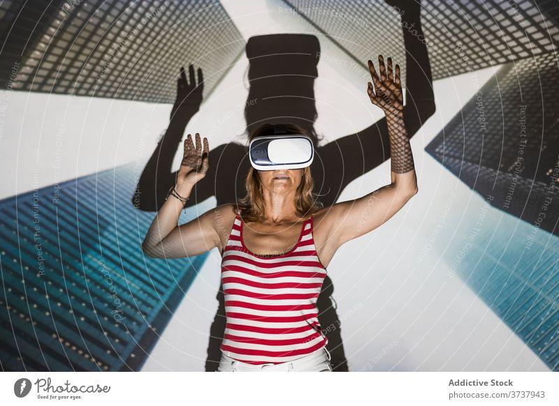 Aufgeregte Frau in VR-Headset erkundet virtuelle Stadt Virtuelle Realität Wolkenkratzer Gebäude Großstadt urban Schutzbrille berühren aufgeregt Erfahrung