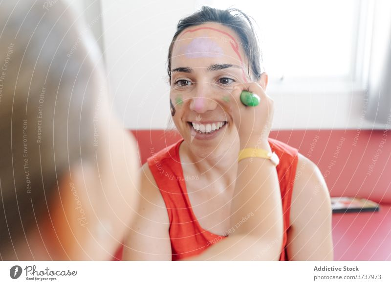 Nettes Mädchen spielt mit Mutter zu Hause Farbe Gesicht unterhalten Spaß haben Tochter heimwärts kreativ Malerei Wochenende wenig Kind Freude niedlich