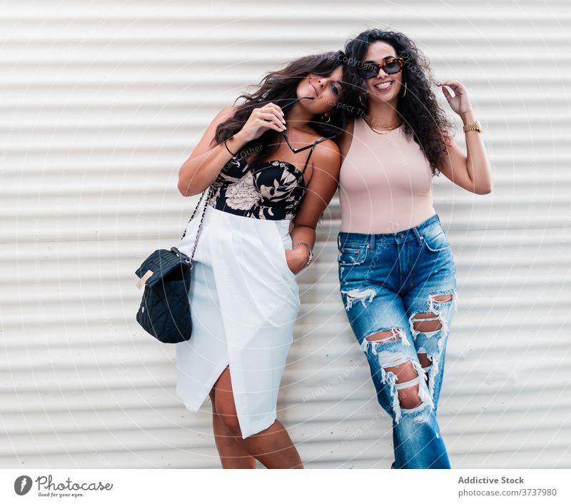 Fröhliche junge Frauen posieren auf der Straße posierend Partnerschaft Freundin Glück Kälte heiter sich[Akk] entspannen ruhen Zusammensein ethnisch Latein