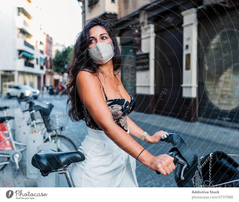 Stilvolle Frau in Schutzmaske mit Fahrrad auf der Straße Mundschutz urban Coronavirus jung COVID Sicherheit neue Normale behüten Krankheit Einschränkung Latein