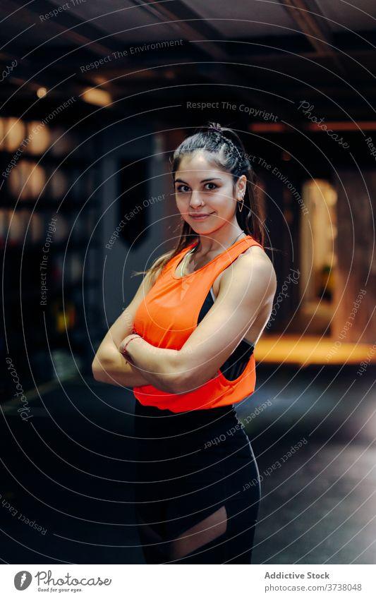 Selbstbewusste fitte Frau im Fitnessstudio stehend sportlich selbstbewusst Bestimmen Sie ernst muskulös stark passen Athlet Sportlerin jung Training Kraft