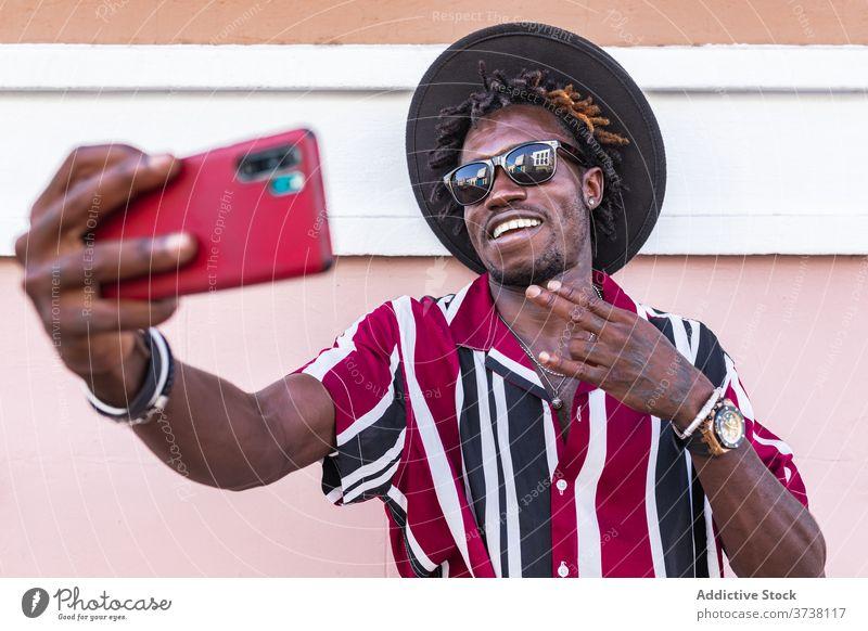 Fröhlich ethnischen Mann in stilvollem Outfit unter Selfie auf der Straße Stil Mode Smartphone heiter trendy flippig Hipster jung Sonnenbrille Streifen modern