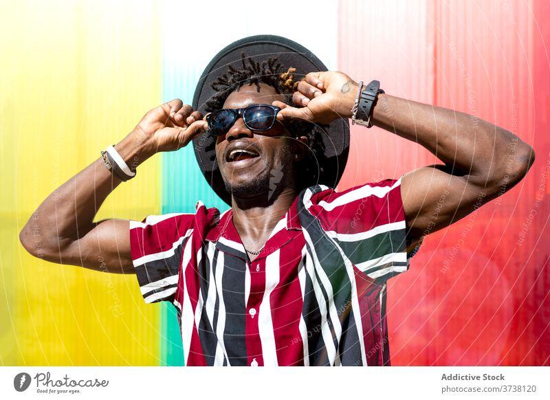 Stilvoller ethnischer Mann mit Sonnenbrille und Hut Mode trendy farbenfroh Streifen jung modern männlich Afroamerikaner schwarz Hipster mehrfarbig selbstbewusst