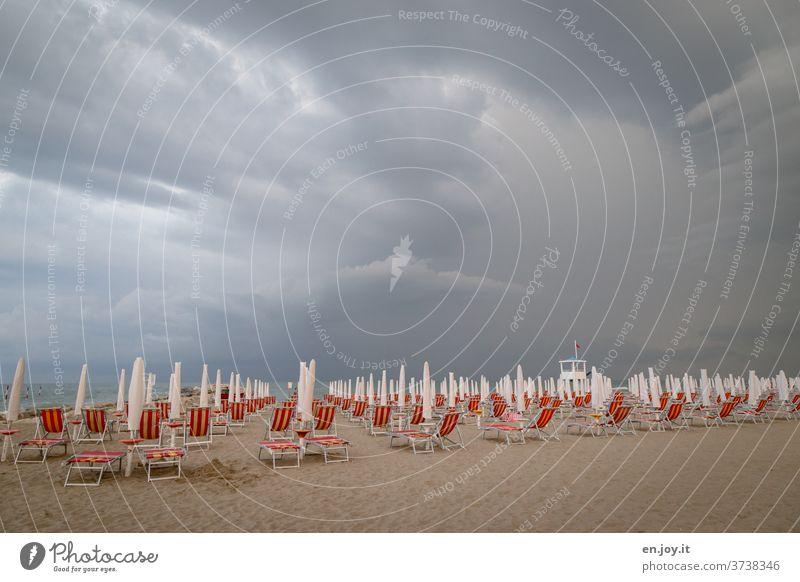 s'isch over - Sommerurlaub - Strand mit Liegestühlen und zugeklappten Sonnenschirmen, da ein unwetterartiges Gewitter mit dunklen Wolken bis zum Horizont am Himmel aufzieht