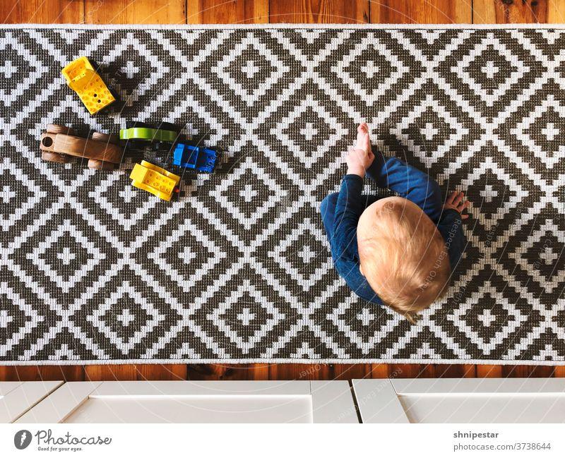 Draufsicht auf ein sitzendes Kleinkind Teppich Spielzeug Lego Duplo Baby Junge Sohn Vater Muster Pattern Fliesen Kacheln Fliesen u. Kacheln teppichmuster Läufer