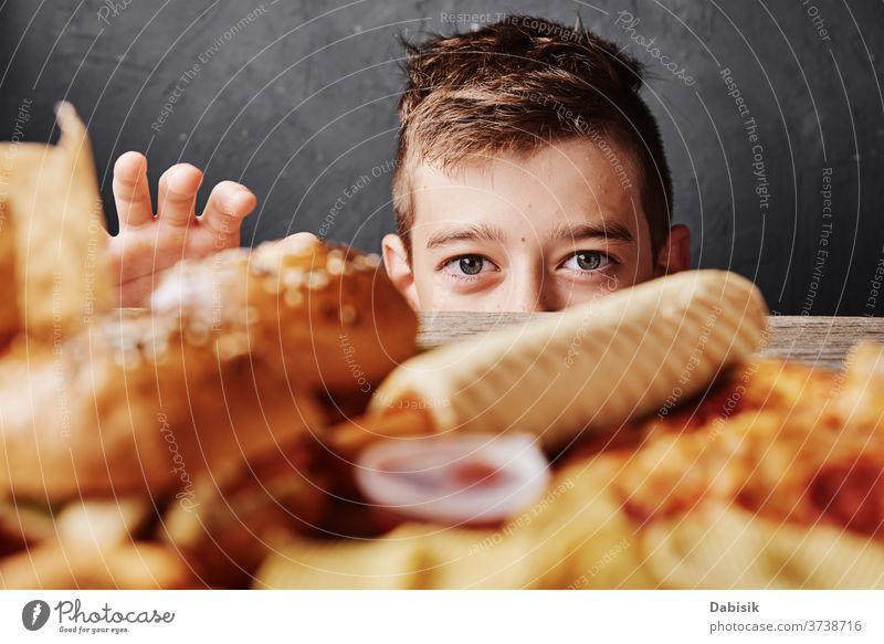 Ein hungriger Junge schaut sich leckeres Essen an und nimmt einen Hamburger vom Tisch. Konzept ungesundes Essen Fett Diät Burger Pizza Hintergrund Cholesterin