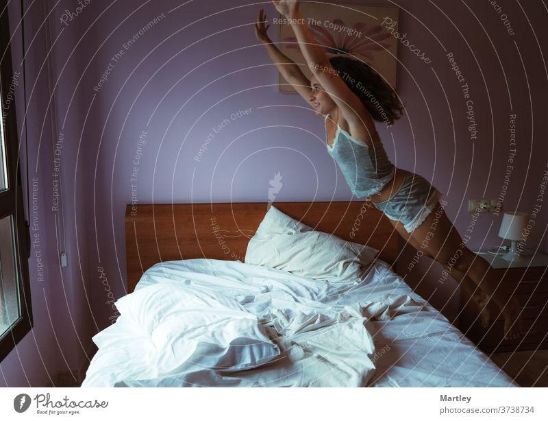 Junge charmante Frau in Schlafklamotten springt auf dem Bett und lacht dabei fröhlich im bequemen Schlafzimmer heimwärts sich[Akk] entspannen Hotel