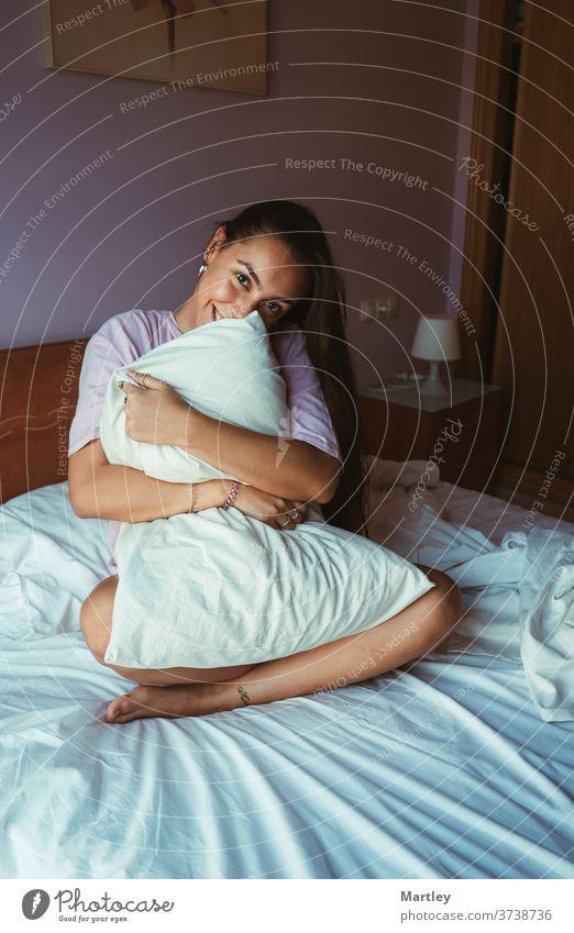 Lächelnde junge Frau in Schlafkleidung, die sich im Sitzen mit dem Kissen bedeckt und mit einem Arm am Kopf auf einem bequemen Bett liegt und sich morgens zu Hause entspannt.