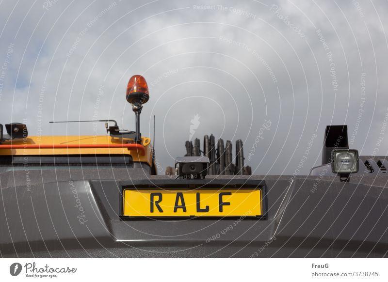 das Baufahrzeug heißt Ralf Baustelle Baustellenfahzeug Name Namensschild Lampen Rundumleuchte Kunststoff Plastik trübes Wetter Himmel