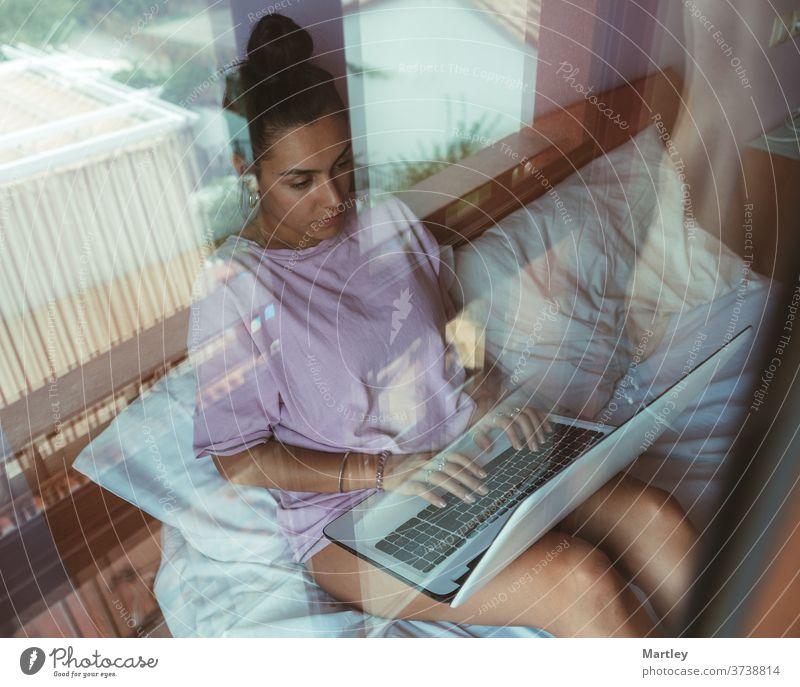 Junge Frau bei der Telearbeit, während sie einen Videogespräch am Laptop führt und auf dem Bett sitzt. Junge Studentin im Online-Unterricht. im Innenbereich