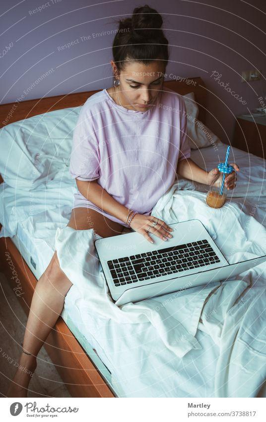 Barfüßige junge Frau im Pyjama, die Telearbeit leistet und erfrischenden Saft genießt, während sie morgens auf einem weichen Bett sitzt und am Laptop stöbert.